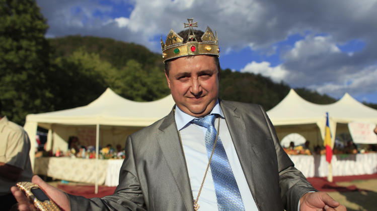 Self proclaimed international king of gypsies Stanescu gestures with his golden plated mobile phone in hand during the traditional ethnic Roma festival in Costesti