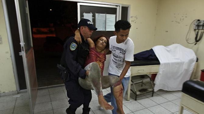 FILE - In this March 11, 2012 file photo, a woman who was injured during a shooting at a pool hall is carried into the Catalino Rivas Public Hospital in San Pedro Sula, Honduras.  A wave of violence has made Honduras among the most dangerous places on Earth, with a homicide rate roughly 20 times that of the U.S. rate, according to a 2011 United Nations report. (AP Photo/Esteban Felix, file)
