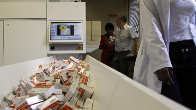 In this photo taken Thursday, Nov. 15, 2012 a newly mechanized pharmaceutical machine that helps pharmacists dispense medicine is loaded with ARV medication, at the US sponsored Themba Lethu, HIV/AIDS Clinic, at the Helen Joseph hospital, in Johannesburg. In the early 90s when South Africa's Themba Lethu clinic could only treat HIV/AIDS patients for opportunistic diseases, many would come in on wheelchairs and keep coming to the health center until they died. Two decades later the clinic is the biggest ARV (anti-retroviral) treatment center in the country and sees between 600 to 800 patients a day from all over southern Africa. Those who are brought in on wheelchairs, sometimes on the brink of death, get the crucial drugs and often become healthy and are walking within weeks.  (AP Photo/Denis Farrell)