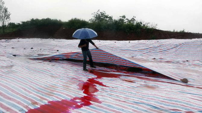 A man lifts plastic sheets covering industrial waste from a closed dye factory which contaminated the water and turned it red, amid heavy rainfall at a mountain in Ruyang county