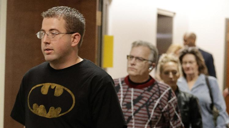 A man wears a Batman shirt as he arrives for court with other victims and family member for Aurora theater shooting suspect James Holmes at the courthouse in Centennial, Colo., on Friday, Jan. 11,  2013.  The judge granted a defense motion to delay the arraignment of Holmes until March 12. The decision comes a day after the judge ruled that Holmes should stand trial. (AP Photo/Ed Andrieski)
