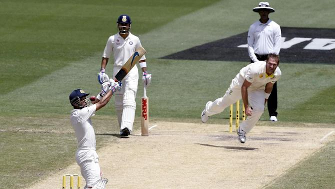 India's Ajinkya Rahane, left, plays at a high delivery from Australia Ryan Harris, right, on the third day of their cricket test match in Melbourne, Australia, Sunday, Dec. 28, 2014. (AP Photo/Andy Brownbill)