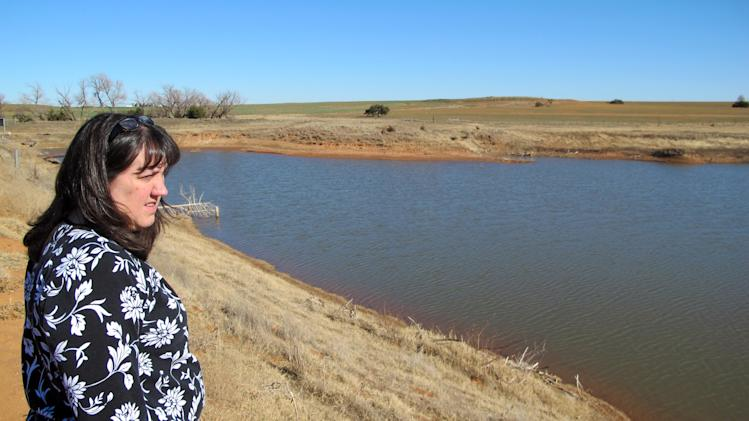 In this Tuesday, Dec. 11, 2012 photo, Caddo County farmer Karen Krehbiel looks over a shrinking pond on the family's farm near Hydro, Okla. Krehbiel said the farm is down about 6 feet because of an ongoing drought, the latest natural disaster to strike the county, which also has been beset in recent years by floods, tornadoes, ice storms and hail. (AP Photo/Sean Murphy)