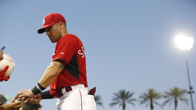 Cincinnati Reds' Skip Schumaker signs autographs for fans prior to the Reds' spring training baseball game against the Milwaukee Brewers on Friday, March 27, 2015, in Goodyear, Ariz. (AP Photo/Ross D. Franklin)