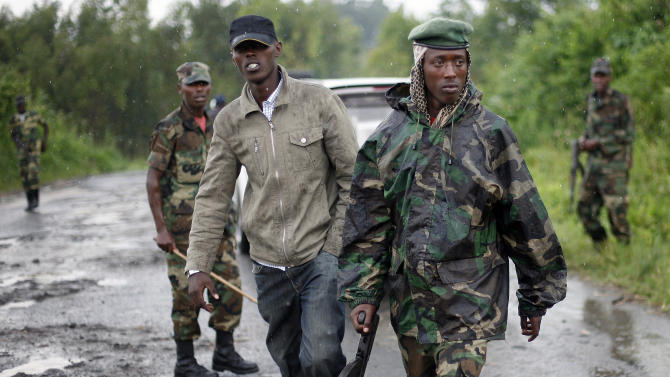 Congolese M23 rebel soldiers are seen on the road to Rushuru near Buhumba some 25 kilometers (16 miles) north of Goma, Thursday, Nov. 22, 2012. Rebel spokesman Lt. Col. Vianney Kazarama vowed Thursday that the fighters would press forward toward seizing the strategic eastern town of Bukavu, which would mark the biggest gain in rebel territory in nearly a decade if it were to fall. (AP Photo/Jerome Delay)
