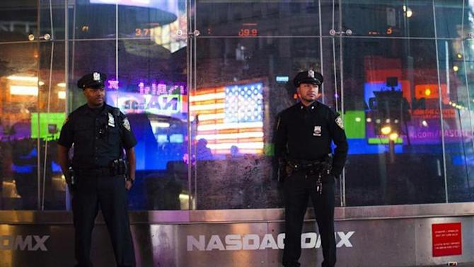 New York police officers stand guard outside NASDAQ MarketSite in New York's Times Square, September 22, 2013. REUTERS/Eduardo Munoz/Files