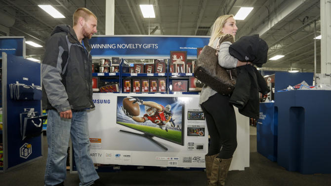 Tony and Sarah Locken carry a television to purchase at Best Buy on Thanksgiving, Thursday, Nov. 26, 2015, in Minnetonka, Minn. (AP Photo/Bruce Kluckhohn)