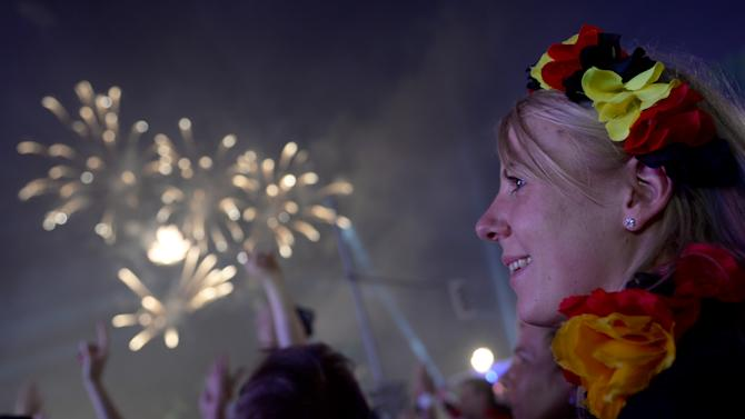 CORRECTS DATE -Fireworks illuminate the sky as German fans celebrate their team after  Germany  won  against Argentina  by 1-0 at the soccer World Cup final in Rio de Janeiro, Brazil,  at a public viewing area called 'Fan Mile'  in Berlin,  early Monday July 14, 2014