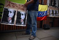 "A supporter of WikiLeaks founder Julian Assange holds a placard with the slogan ""We are all Assange"" written in Spanish outside the Ecuadorian embassy in central London on June 21, 2012, where Assange is still holed up seeking political asylum"