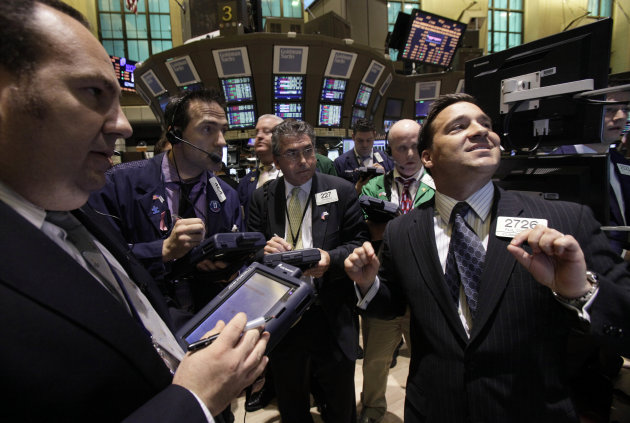 FILE - In a March 21, 2012 file photo, Specialist Paul Cosentino, right, directs trading on the floor of the New York Stock Exchange. Stocks closed mostly lower Tuesday Aug. 14, 2012, after trading sl