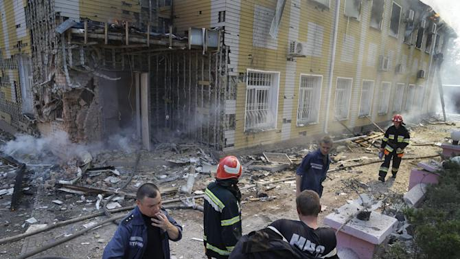 Ukrainian fire fighters put out the fire at the destroyed building after shelling in Donetsk