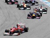 Spain's Ferrari driver Fernando Alonso, left, leads Germany's Red Bull driver Sebastian Vettel, center, and Germany's Mercedes driver Michael Schumacher, right, right after the start of the German F1 Grand Prix in Hockenheim, Germany,  Sunday, July 22, 2012. (AP Photo/Michael Probst)