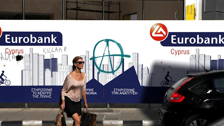 A woman crosses a busy shopping street in front of a Eurobank branch currently under construction in the heart of Cyprus' capital Nicosia on Thursday, Oct. 31, 2013. A commission of experts says bailed-out Cyprus should offer a European Union-backed state guarantee on all deposits once it removes limits on money flows. (AP Photo/Petros Karadjias)