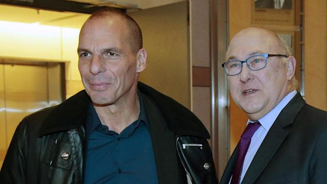 Greek Finance Minister Yanis Varoufakis, left, is greeted by his French counterpart Michel Sapin, at the Economy Ministry in Paris, Sunday Feb. 1, 2015. Finance Minister Yanis Varoufakis, who had a tense meeting with Eurogroup leader Jeroen Dijsselbloem in Athens on Friday, has brought forward a trip to Paris, London and Rome to meet his counterparts. (AP Photo/Jacques Demarthon, Pool)