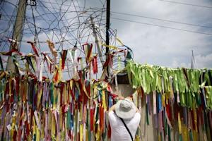 A tourist hangs a ribbon bearing messages wishing the …
