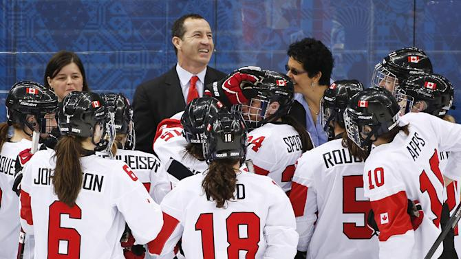 Canada head coach Kevin Dineen celebrates with players after Canada beat Switzerland 3-1 in a 2014 Winter Olympics women's semifinal ice hockey game at Shayba Arena, Monday, Feb. 17, 2014, in Sochi, Russia