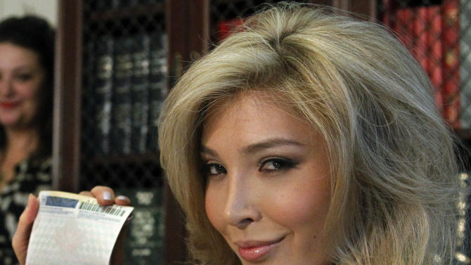 """FILE - In this April 3, 2012, file photo, Jenna Talackova, who advanced to the finals of the Miss Canada competition, part of the Miss Universe contest, shows her passport that lists her gender as female, during a news conference in Los Angeles. Talackova says she was forced out of the competition because Pageant officials alleged she was not """"a naturally-born female."""" Transgender women will be allowed to participate in the Miss Universe beauty pageant next year, officials announced Tuesday, April 10, a week after they ruled Talackova could vie for the crown this year. (AP Photo/Reed Saxon, File)"""