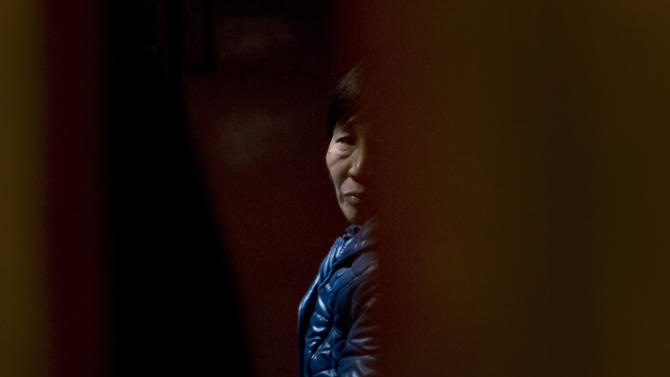 A Chinese relative of passengers aboard a missing Malaysia Airlines plane looks out as she waiting for the latest news inside a hotel room for relatives or friends of passengers aboard the missing airplane in Beijing, China Tuesday, March 11, 2014. Nearly three days after the Boeing 777 with 239 people on board disappeared en route from Kuala Lumpur to Beijing, no debris has been seen in Southeast Asian waters. (AP Photo/Andy Wong)