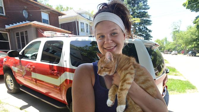 In this June 15, 2014 photo, Tara Dennis, 21, poses for a photo with a cat after Erie firefighters rescued her after she got stuck while trying to rescue the cat that was stuck in a tree in the 1000 block of West Eighth Street in Erie, Pa. (AP Photo/Erie Times-News, Jack Hanrahan)