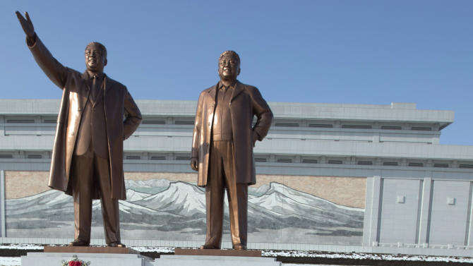 North Koreans wear their hats after bowing in front of the statues of late leaders, Kim Il Sung, left, and Kim Jong Il, at Mansu Hill in Pyongyang, North Korea, Monday, Dec. 17, 2012. Sirens wailed for three minutes at noon Monday in honor of the first anniversary of the death of Kim Jong Il. (AP Photo/Ng Han Guan)