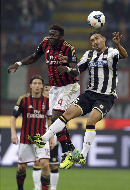 AC Milan's Sulley Muntari, left, and Udinese's Gianfranco Pinzi jump for the ball, during a Serie A soccer match between AC Milan and Udinese, at the San Siro stadium in Milan, Italy, Saturday, Oct. 1