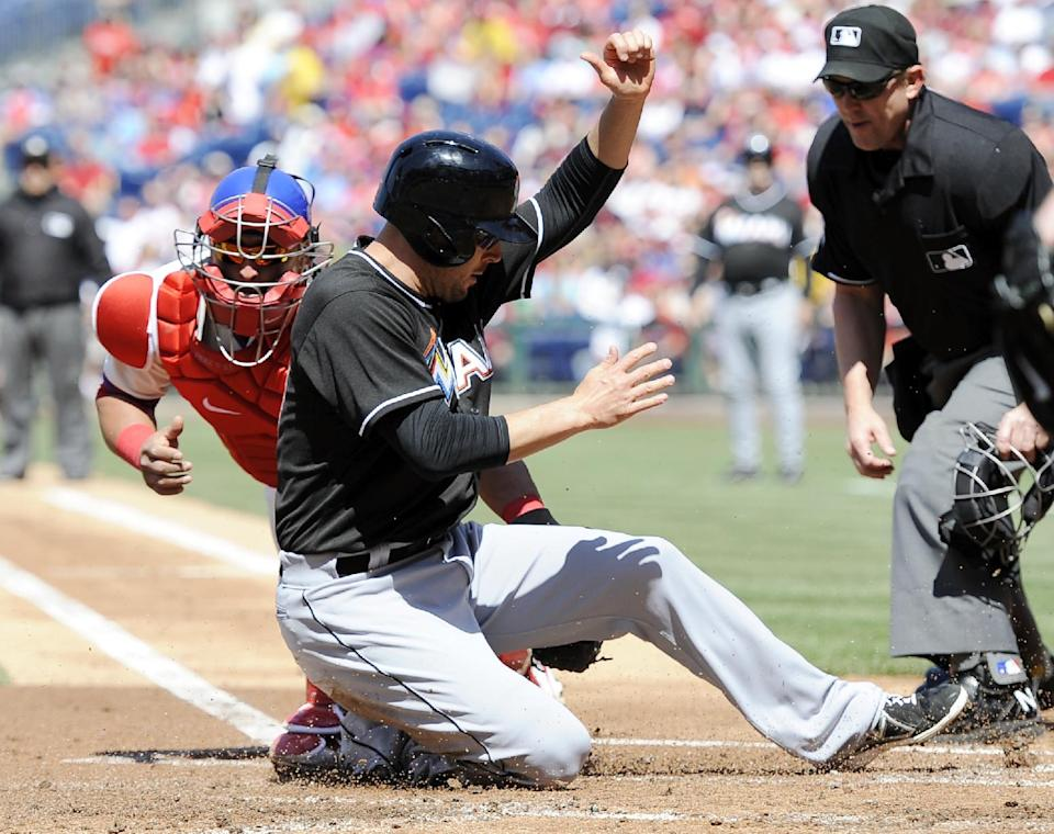 Miami Marlins' Greg Dobbs, foreground, slides past Philadelphia Phillies' Carlos Ruiz,  left, and scores a run in the first inning of a baseball game on Sunday, May 5, 2013, in Philadelphia. (AP Photo/Michael Perez)