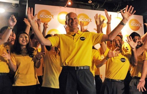<p>This file photo shows Scoot's chief executive Campbell Wilson (C) celebrating at the unveiling of the new low-cost carrier, in Singapore, in 2011. Scoot has taken off for the first time, using a novel way of saving fuel -- by replacing its in-built TVs with iPads.</p>