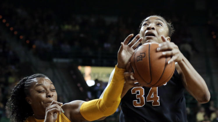 Baylor guard Odyssey Sims (0) blocks a drive to the basket by Texas 's Imani McGee-Stafford (34) in the first half of an NCAA college basketball game Saturday, Feb. 23, 2013, in Waco, Texas. (AP Photo/Tony Gutierrez)