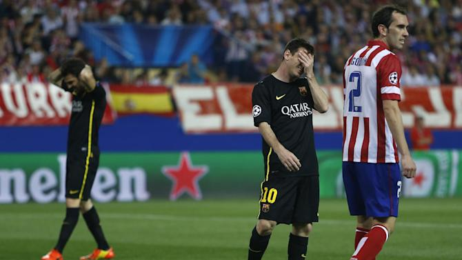 Barcelona's Lionel Messi and Cesc Fabregas react next to Atletico's Diego Godin, right, during the Champions League quarterfinal second leg soccer match between Atletico Madrid and FC Barcelona at the Vicente Calderon stadium in Madrid, Spain, Wednesday, April 9, 2014