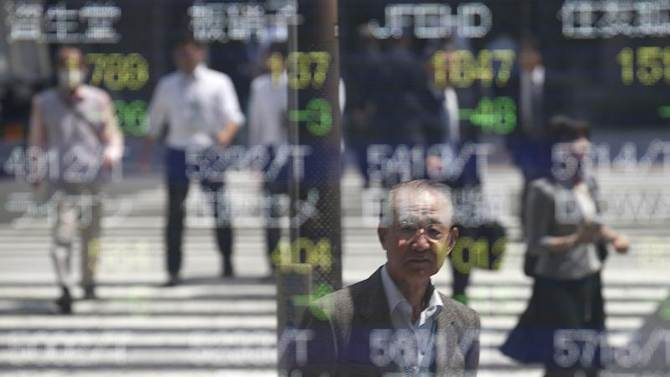 People are reflected on a stock quotation board outside a brokerage in Tokyo
