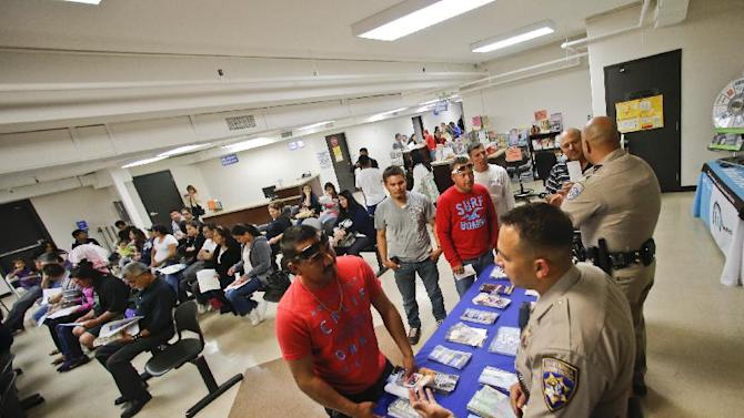 FILE - In this Wednesday, April 23, 2014 file photo, California Highway Patrol officers Armando Garcia, right, and Ray Patton explain to immigrants the process of getting a drivers license during an information session at the Mexican Consulate, in San Diego. California is gearing up to start issuing driver's licenses to immigrants in the country illegally in a bid to make the roads safer that could also give more than a million people access to state-issued identification. (AP Photo/Lenny Ignelzi,File)