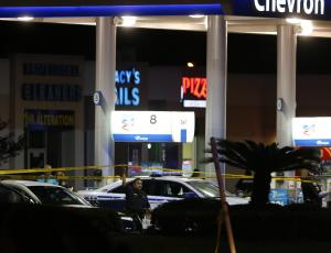 Officials investigate the scene at a gas station where …