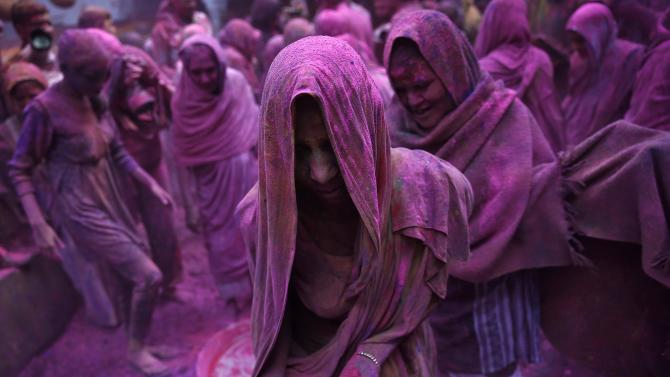 Widows daubed in colours take part in the Holi celebrations organised by non-governmental organisation Sulabh International at a widows' ashram at Vrindavan