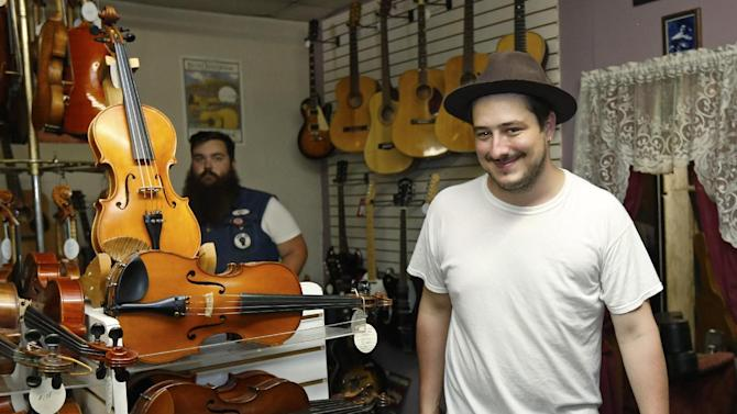 In this Sept. 5, 2013, photo Marcus Mumford, of the band Mumford & Sons, walks through Byron Berline's Double Stop Fiddle Shop in Guthrie,, Okla. The population of the small Oklahoma town is expected to quadruple this weekend as people come to watch the British folk rock band on the second stop of the Mumford & Sons' Gentlemen of the Road concert series in Guthrie. (AP Photo/Sue Ogrocki)