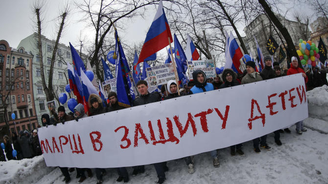 """Demonstrators carry Russian flags and a huge poster reading """"March in Defense of Children"""" during a massive rally in Moscow, Saturday, March 2, 2013. Russia voiced strong skepticism Saturday about the U.S. autopsy on Max Shatto, a 3-year-old adopted Russian boy in Texas and demanded further investigation as thousands rallied in Moscow to support the Kremlin ban on U.S. adoptions of Russian children. (AP Photo/Alexander Zemlianichenko)"""