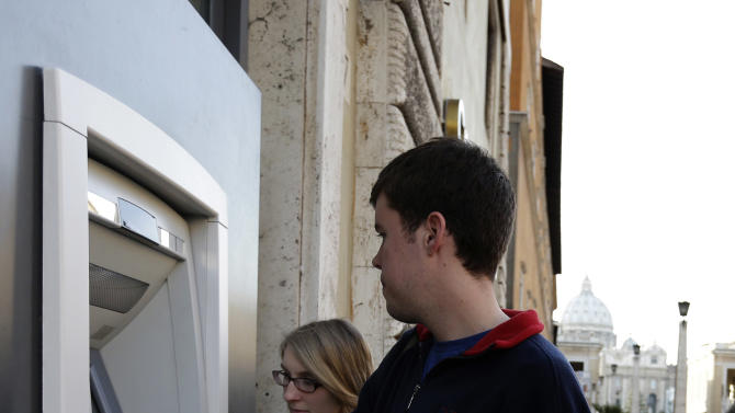 """Ben Kiniry, of Texas, gets cash from an ATM machine along Via della Conciliazione, the main road leading to St. Peter's Basilica at the Vatican, Thursday, Jan. 3, 2013. It's """"cash only"""" now for tourists at the Vatican wanting to pay for museum tickets, souvenirs and other services after Italy's central bank decided to block electronic payments, including credit cards, at the tiny city state. The Italian daily Corriere della Sera reported Thursday that Bank of Italy took the action because the Holy See has not yet fully complied with European Union safeguards against money laundering. That means Italian banks are not authorized to operate within the Vatican, which is in the process of improving its mechanisms to combat laundering. The Vatican says it's scrambling to find a non-Italian bank to provide the electronic payment services """"quite soon"""" but declined to discuss Bank of Italy's concerns. The central bank had no immediate comment on the situation. (AP Photo/Alessandra Tarantino)"""