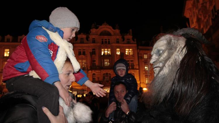 A child reacts to a reveller dressed as a devil at the Old Town Square in Prague