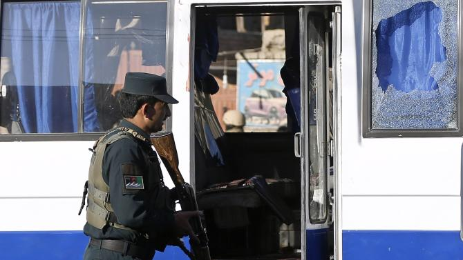 Afghan policeman inspects bloodstains inside a bus which was hit by a remote-controlled bomb at the site of an incident in Kabul