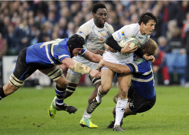 Bath's Stuart Hooper, left, and Lewis Moody, right, combine to tackle Montpellier's Francois Trinh-Duc, 2nd right, during their Heineken Cup pool 3 rugby match at the Recreation ground, Bath, England,