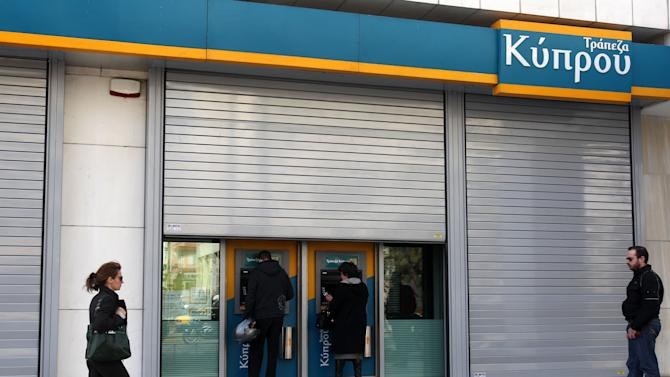 Customers of Bank of Cyprus use the ATMs at the headquarter offices as the bank will remain closed for two days in Athens, Tuesday, March 19, 2013. Banks stocks were sharply lower on the Athens Stock Exchange, as trading resumed for the first time in Greece since the details of a bailout in Cyprus and a shock levy on bank deposits were announced. Following a public holiday Monday, Greek branches of the Cypriot lenders the Bank of Cyprus, Laiki Bank and Hellenic remained closed Tuesday and Wednesday. (AP Photo/Thanassis Stavrakis)