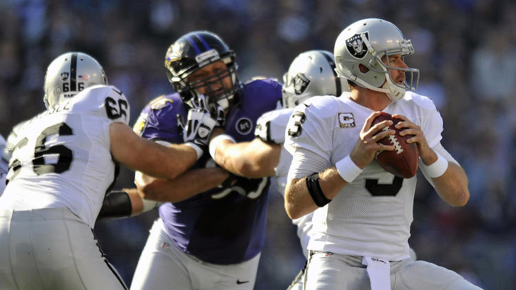 Oakland Raiders quarterback Carson Palmer (3) looks for a receiver as teammates hold back Baltimore Ravens nose tackle Ma'ake Kemoeatu, second from left, in the first half of an NFL football game in Baltimore, Sunday, Nov. 11, 2012. (AP Photo/Gail Burton)
