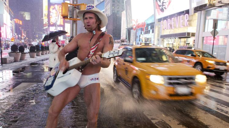 "Robert Burck, aka the ""Naked Cowboy,"" performs in Times Square as it snows Friday, Feb. 8, 2013, in New York. Snow began falling across the Northeast on Friday, ushering in what was predicted to be a huge, possibly historic blizzard and sending residents scurrying to stock up on food and gas up their cars. The storm could dump 1 to 3 feet of snow from New York City to Boston and beyond.  (AP Photo/Frank Franklin II)"