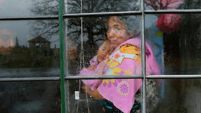 """Fanyumi Lopez, 38, covers up with a towel and hugs her 4-year-old daughter Rucelmi looking out her window as the family waits for help after a tree fell on and destroyed half their mobile home in Jack Craig's Trailer Park in Adairsville, Ga. in an apparent tornado on Wednesday, Jan. 30, 2013. Lopez said """" I prayed everything will come back to normal and at the end a door will open"""" during the storm. She was alone when the storm hit. (AP Photo/Atlanta Journal-Constitution, Curtis Compton )"""