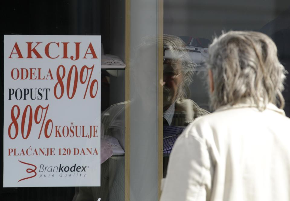 An elderly man is looking at a poster advertising an 80 percent discount on winter collection at a shop in downtown Belgrade, Serbia, Monday, March 19, 2012. Winter sales have extended well into March in Serbia and other countries in the region because of the economic crisis and a long and cold winter. (AP Photo/Darko Vojinovic)