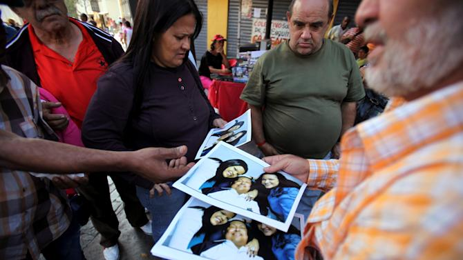 A man sells prints at 20 bolivars each, about 3.00 U.S. dollars, of one of the photographs released Friday by the Venezuelan government showing President Hugo Chavez with his daughters Maria Gabriela, left, and Rosa Virginia, right, at Bolivar square in Caracas, Venezuela, Friday, Feb. 15, 2013. Amid widespread speculation and rumors in Venezuela about Chavez's delicate condition following his Dec. 11 cancer surgery, the government released the first photos of the ailing president in more than two months on Friday, presenting images of him smiling alongside his daughters in Cuba. (AP Photo/Fernando Llano)
