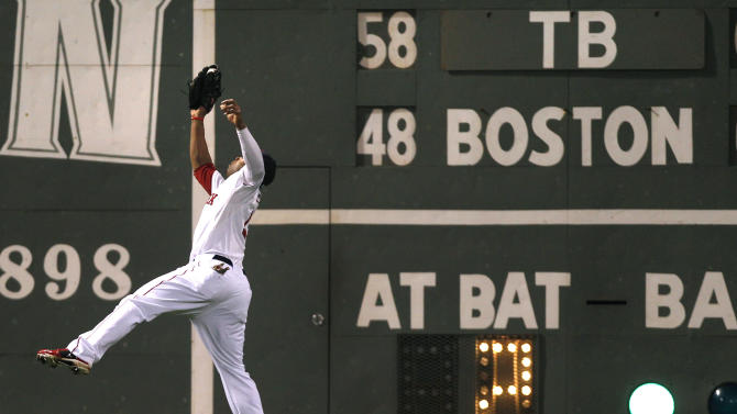 Boston Red Sox left fielder Carl Crawford makes a leaping catch on a line drive to the warning track by Tampa Bay Rays' B.J. Upton during the fifth inning of a baseball game at Fenway Park in Boston, Thursday, Sept. 15, 2011. (AP Photo/Charles Krupa)