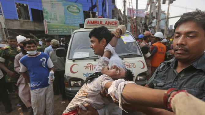 A Bangladeshi rescue worker, who was injured during a stampede caused by crowd panic over the rumor a section of the building might collapse, is carried at the site of a building that collapsed Wednesday in Savar, near Dhaka, Bangladesh, Friday, April 26, 2013. The death toll reached hundreds of people as rescuers continued to search for injured and missing, after a huge section of an eight-story building that housed several garment factories splintered into a pile of concrete. (AP Photo/Kevin Frayer)