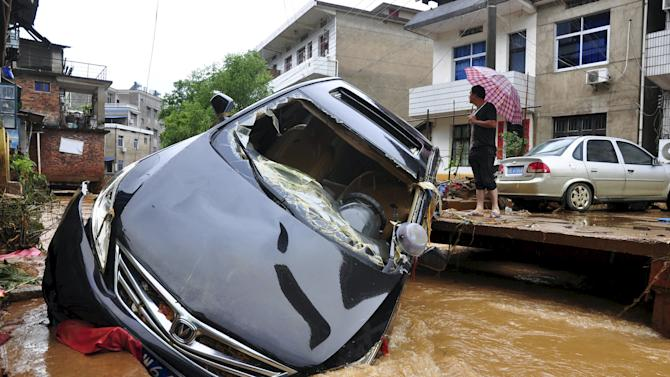 A damaged car is stuck in a flooded river after a heavy rainfall in Dexing