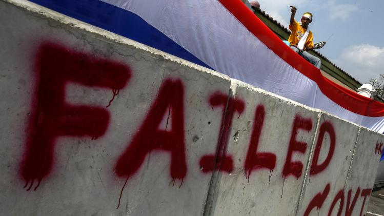An anti-government protester puts a large Thai national flag on the gate and fence around Government House in Bangkok