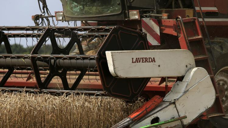 A French farmer drives his combine as he harvests wheat in a field in Beaucamps-le-Vieux, northern France